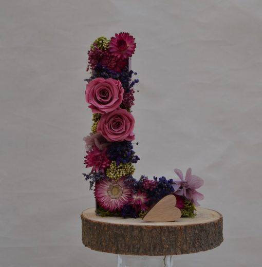 Letra L de flores preservadas en peana